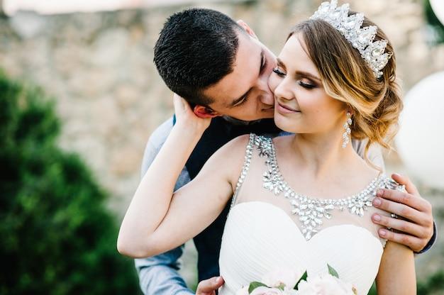 Молодожены обнимаются и целуются. мужчины обнимают женщину сзади и целуют его в щеку. Premium Фотографии