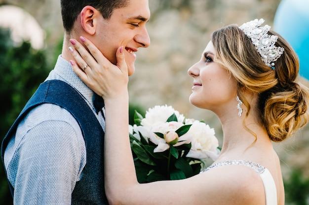 Стильная счастливая невеста и жених. молодожены обнимаются. Premium Фотографии