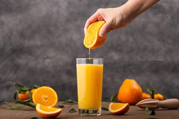 オレンジジュースのグラスとオレンジを絞る人 無料写真