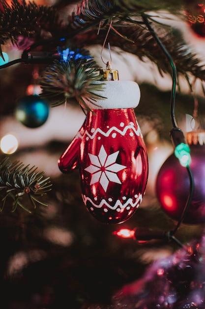クリスマスグローブの垂直のクローズアップショット形の木からぶら下がっている飾り 無料写真