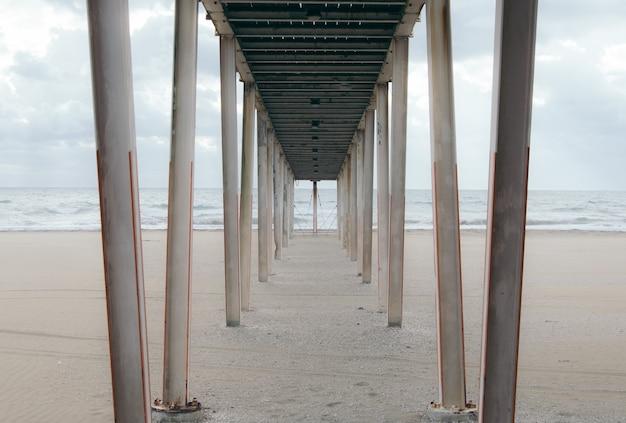 曇りの日に砂浜で木製の桟橋の下 無料写真