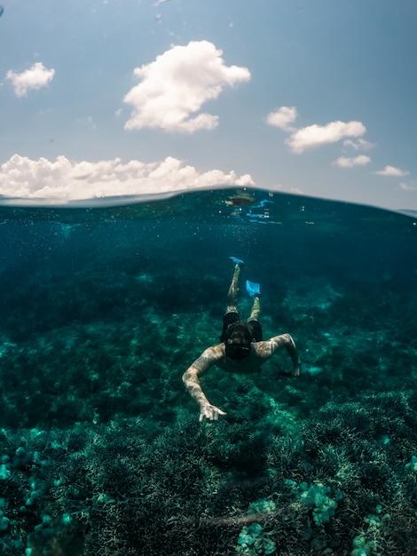 Вертикальный выброс мужчины плавание под водой с неба на заднем плане Бесплатные Фотографии