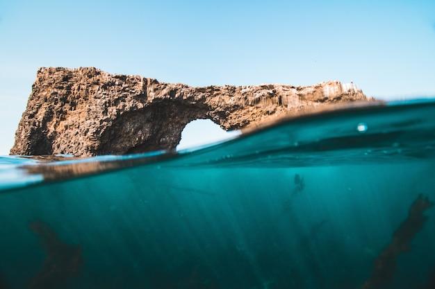 晴れた日に海で岩やサンゴ礁の水面レベルのショット 無料写真
