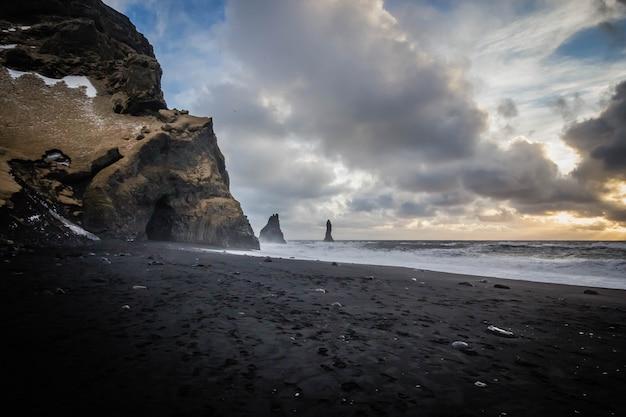 アイスランドのヴィークにある海の美しい海岸。息をのむような雲と岩が側面にあります。 無料写真