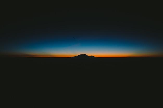 Красивый снимок темных холмов с изумительным оранжевым и синим закатом на горизонте Бесплатные Фотографии