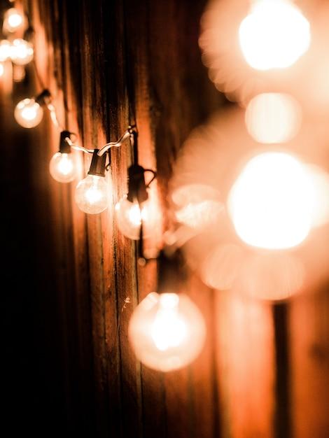 木製のフェンスの近くの電線に点灯している電球の垂直方向のショット 無料写真