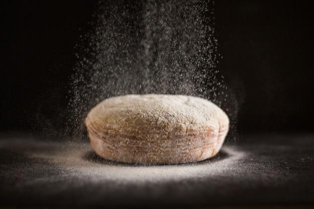 焼きたてのパンに小麦粉を振りかける 無料写真