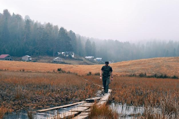 Мужчина гуляет по узкой деревянной тропе посреди сухого травянистого поля с деревьями Бесплатные Фотографии