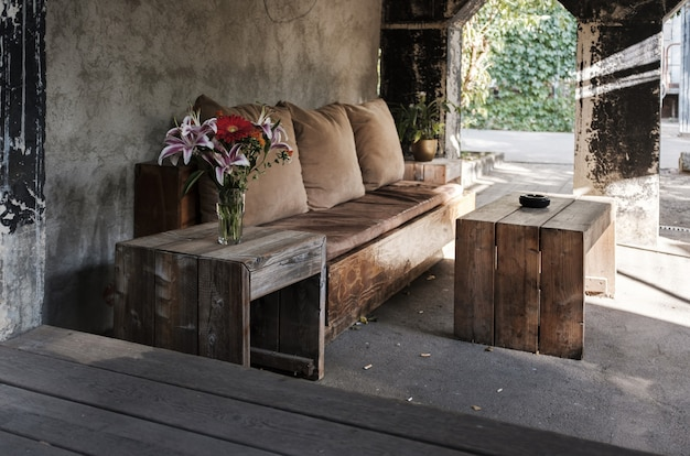 枕とテーブル付きの居心地の良い屋外ベンチ 無料写真