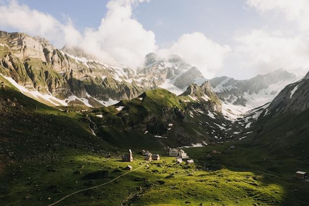 Красивый снимок зеленых гор, покрытых снегом под небом с белыми облаками Бесплатные Фотографии
