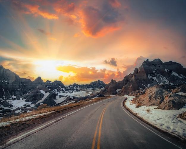 Красивая перспектива узкой сельской дороги со скалистыми горами, покрытыми снегом на расстоянии Бесплатные Фотографии