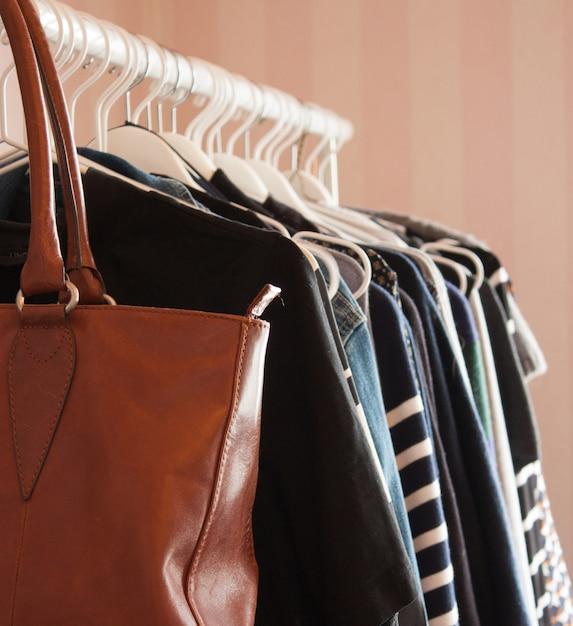 茶色の革のバッグと白いハンガーに絞首刑にされた服の垂直のクローズアップ 無料写真
