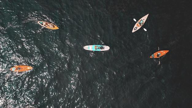 Накладные выстрелы людей в маленьких лодках в воде Бесплатные Фотографии