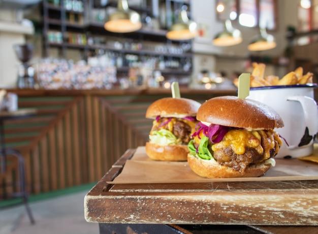 Крупным планом гамбургеры на деревянный поднос с размытым фоном Бесплатные Фотографии