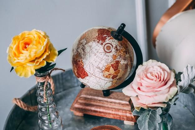 Выстрел из коричневого земного шара рядом с желтыми и розовыми розами в вазах Бесплатные Фотографии