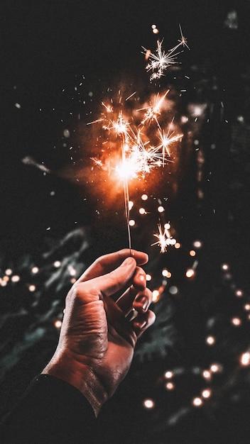 Мужская рука держит сверкающую палку с темным фоном Бесплатные Фотографии