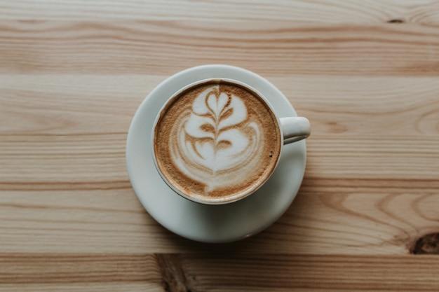 Макрофотография выстрел из кофе с латте арт в белой керамической чашки на деревянном столе Бесплатные Фотографии