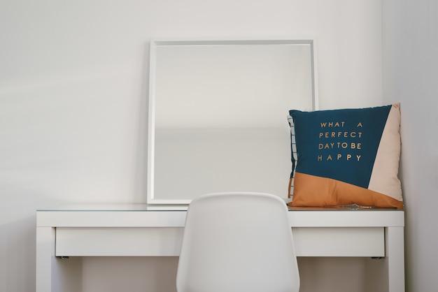 Зеркало и подушка на белом столе со стулом впереди Бесплатные Фотографии