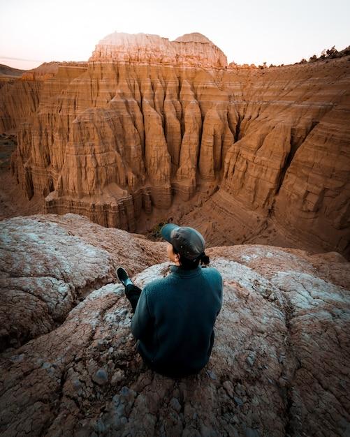 Самка сидит на краю скалы с удивительно высокими скалистыми горами Бесплатные Фотографии