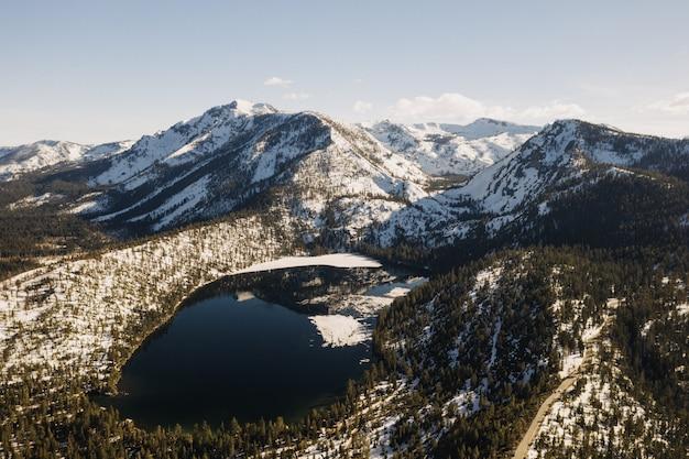 Красивый широкий снимок гор, покрытых снегом, в окружении деревьев и озера Бесплатные Фотографии