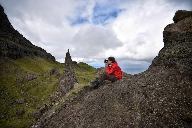 山の岩の上に座って写真を撮る写真家 無料写真