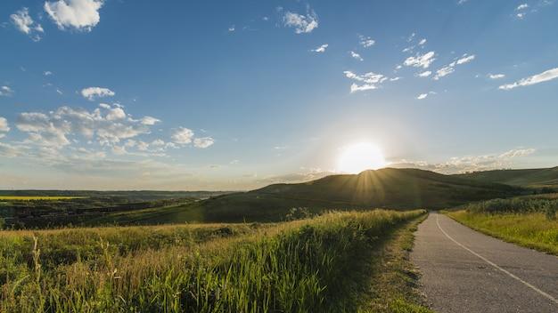 草と澄んだ空と山の近くの道路の美しいショット 無料写真
