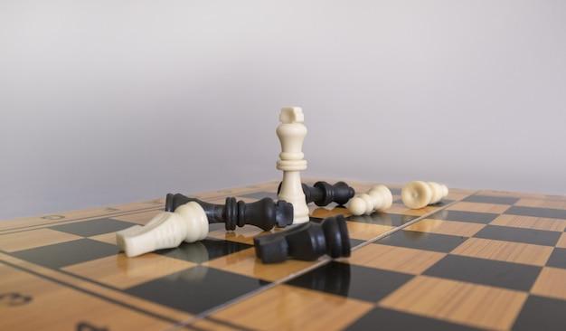 Макрофотография выстрел из шахматных фигурок на шахматной доске с размытым белым фоном Бесплатные Фотографии
