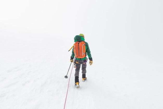山の急な雪の斜面を歩くスキーヤー 無料写真