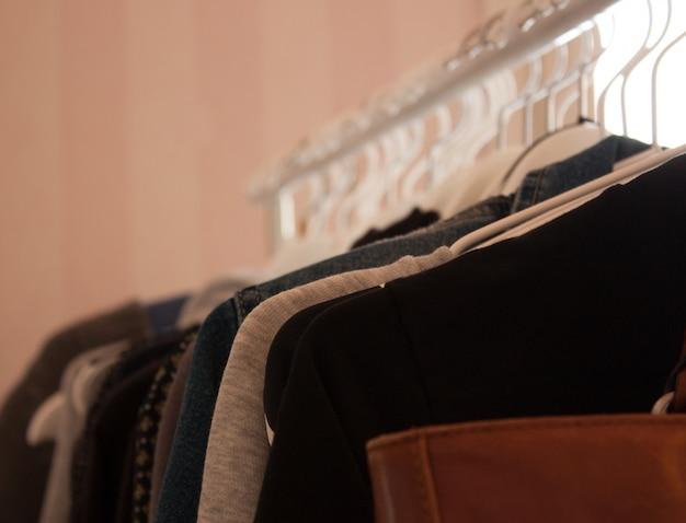 茶色の革のバッグと白いハンガーに絞首刑にされた服のクローズアップ 無料写真