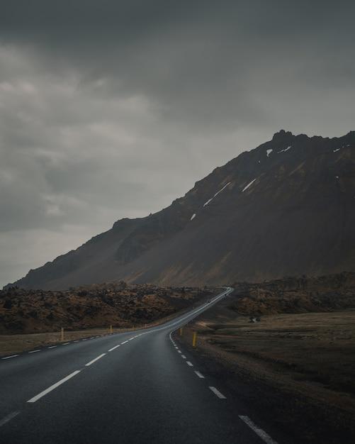 灰色の暗い空の下で美しいロッキー山脈の横にある空の曲がりくねった道 無料写真