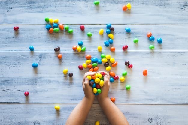 Детские руки держат кучу разноцветных конфет Бесплатные Фотографии