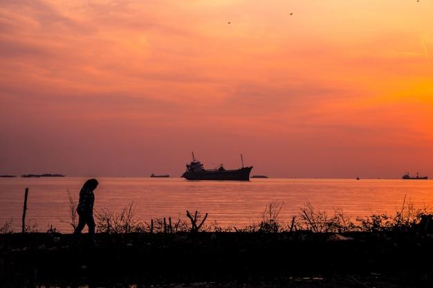 Самка гуляет по берегу моря с кораблем в воде на рассвете Бесплатные Фотографии