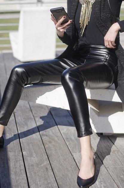 黒革のズボンと金のネックレスを身に着けている携帯電話を押しながら座っている女性のショット 無料写真