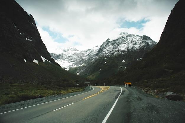 Пышная дорога в сельской местности со снежными горами и красивыми облаками в небе Бесплатные Фотографии