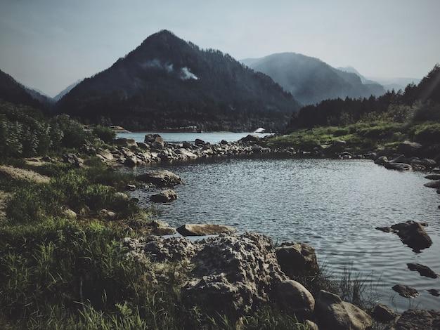 背景の山と水の真ん中に岩が多い経路 無料写真