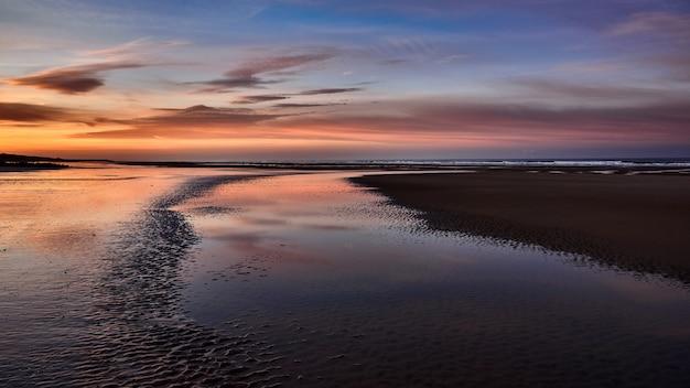 黄金の時間の間に素晴らしい曇り空と海の美しい海岸のワイドショット 無料写真