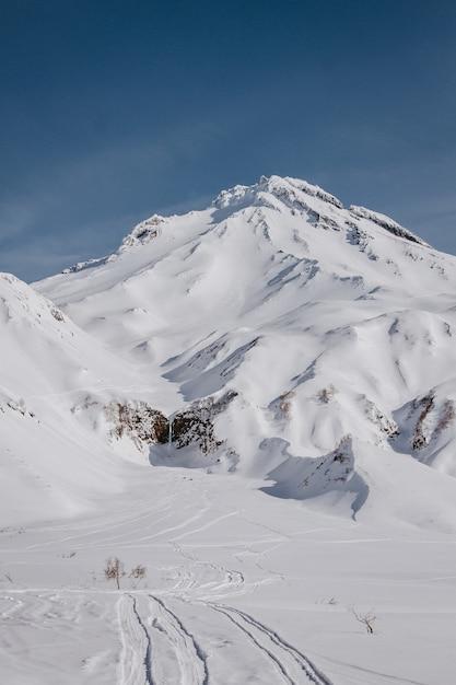 背景の青い空と急な丘から撮影した美しい雪に覆われた山の垂直ショット 無料写真
