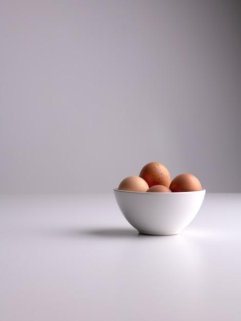 白い表面と灰色のきれいな背景に茶色の卵が入った白いボウルの垂直ショット 無料写真