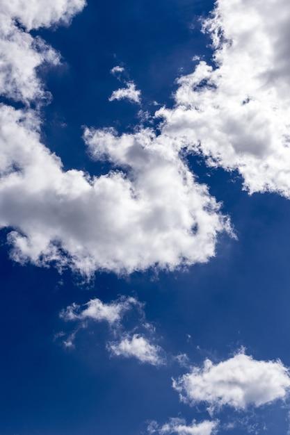 息をのむような大きな白い雲と美しい青い空の垂直ショット 無料写真