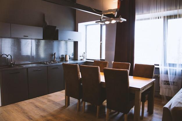 黒のインテリアとキッチンの窓のカーテンの近くの木製の椅子と木製のテーブルのショット 無料写真