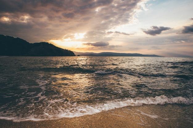 日没時に空の下で遠くに山の近くの海の広い風景ショット 無料写真