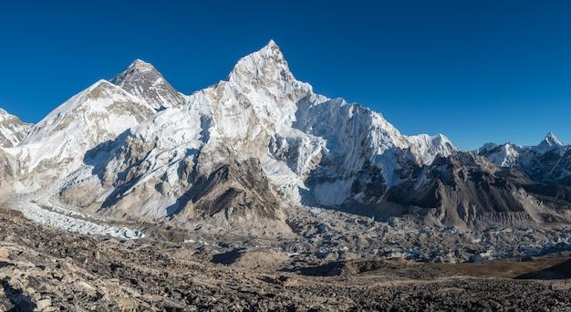 Пейзаж выстрел из красивой долины, окруженной огромными горами со снежными вершинами Бесплатные Фотографии