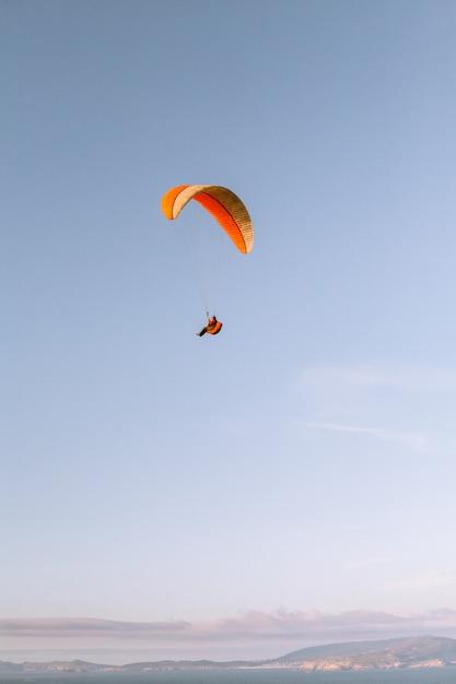 美しい青い空の下をパラシュートで下る孤独な人の垂直方向のショット 無料写真