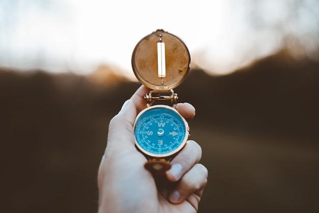 Макрофотография выстрел человека, держащего компас с размытым фоном Бесплатные Фотографии