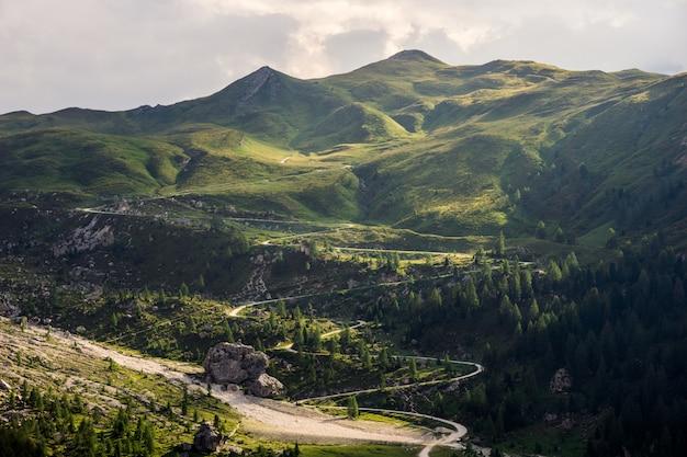 Извилистая дорога до горы, окруженной деревьями в дневное время Бесплатные Фотографии