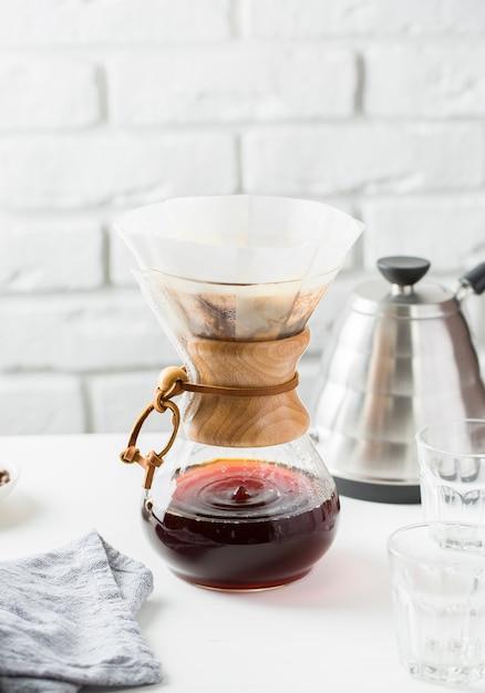 テーブルの上の灰色のやかんの近くのガラスコーヒーピッチャー 無料写真