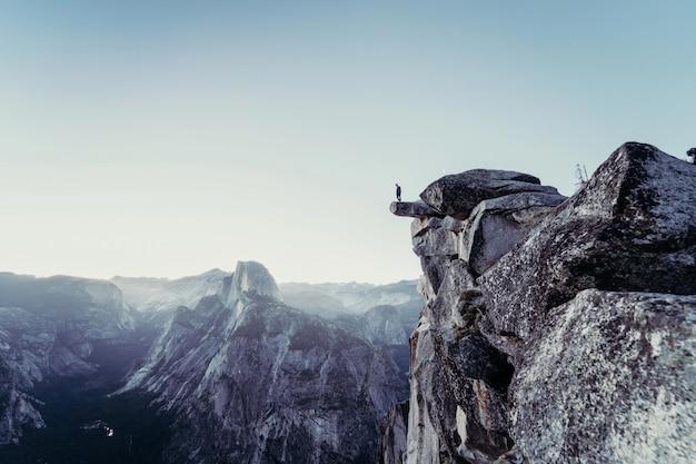 Красивый снимок скалистых гор с человеком, стоящим на краю Бесплатные Фотографии