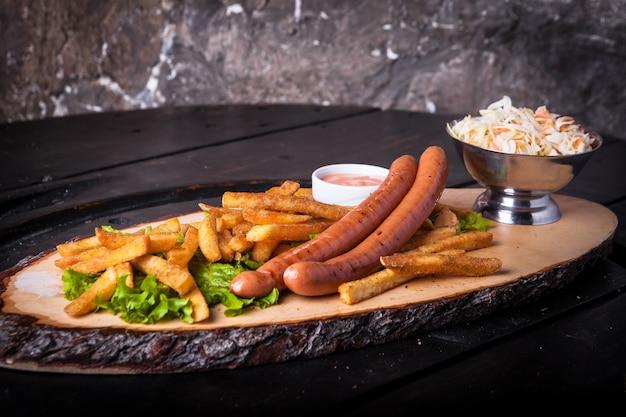 Жареные сосиски, картофель фри, кетчуп и салат на разделочной доске Бесплатные Фотографии