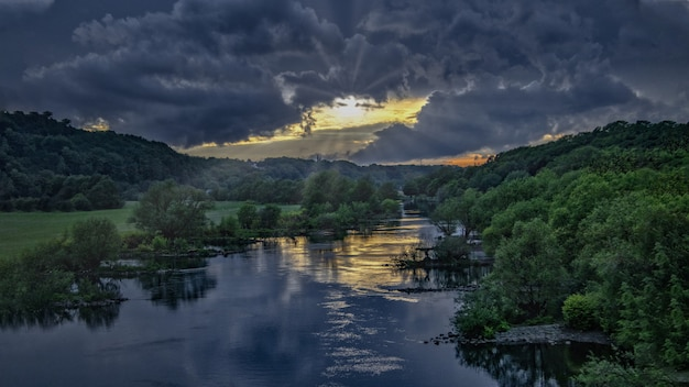 暗い空の下で緑の森の真ん中にある川で息をのむサネット 無料写真