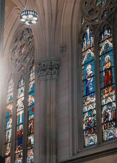 灰色の壁と窓に宗教聖人のモザイク画が描かれた教会の内部 無料写真